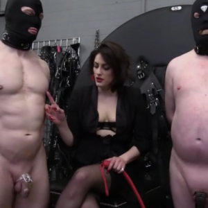 Mistress controlling 2 hooded slaves with chastity